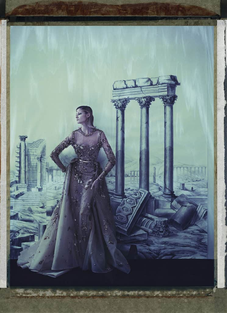 Fine art color photography of fashion model wearing haute couture by Elie Saab in front of a painted wallpaper depicting a the temple ruins of Palmyra, Syria. Wallpaper by de Gournay.