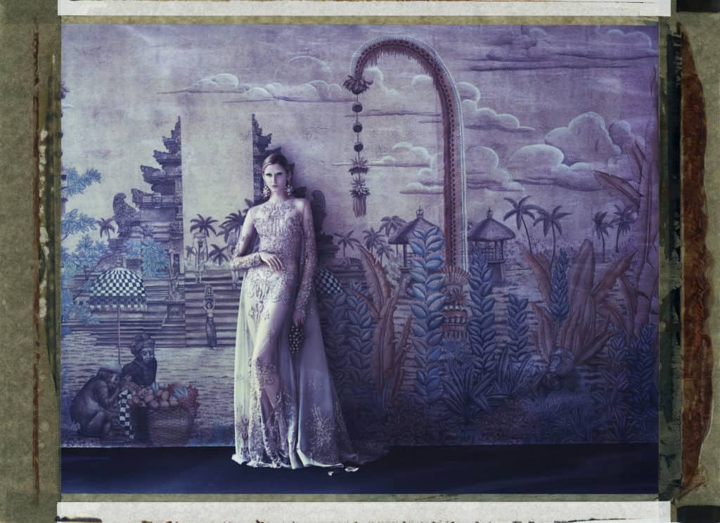 Fine art color photography of fashion model wearing haute couture by Elie Saab in front of a painted wallpaper depicting a temple in Bali. Wallpaper by de Gournay.