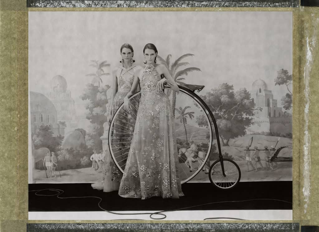 Fine art b/w photography of two twin fashion models wearing haute couture by Elie Saab, with a historic high wheeler bicycle, in front of a painted Wallpaper depicting the city of Jaipur, India. Wallpaper by de Gournay.