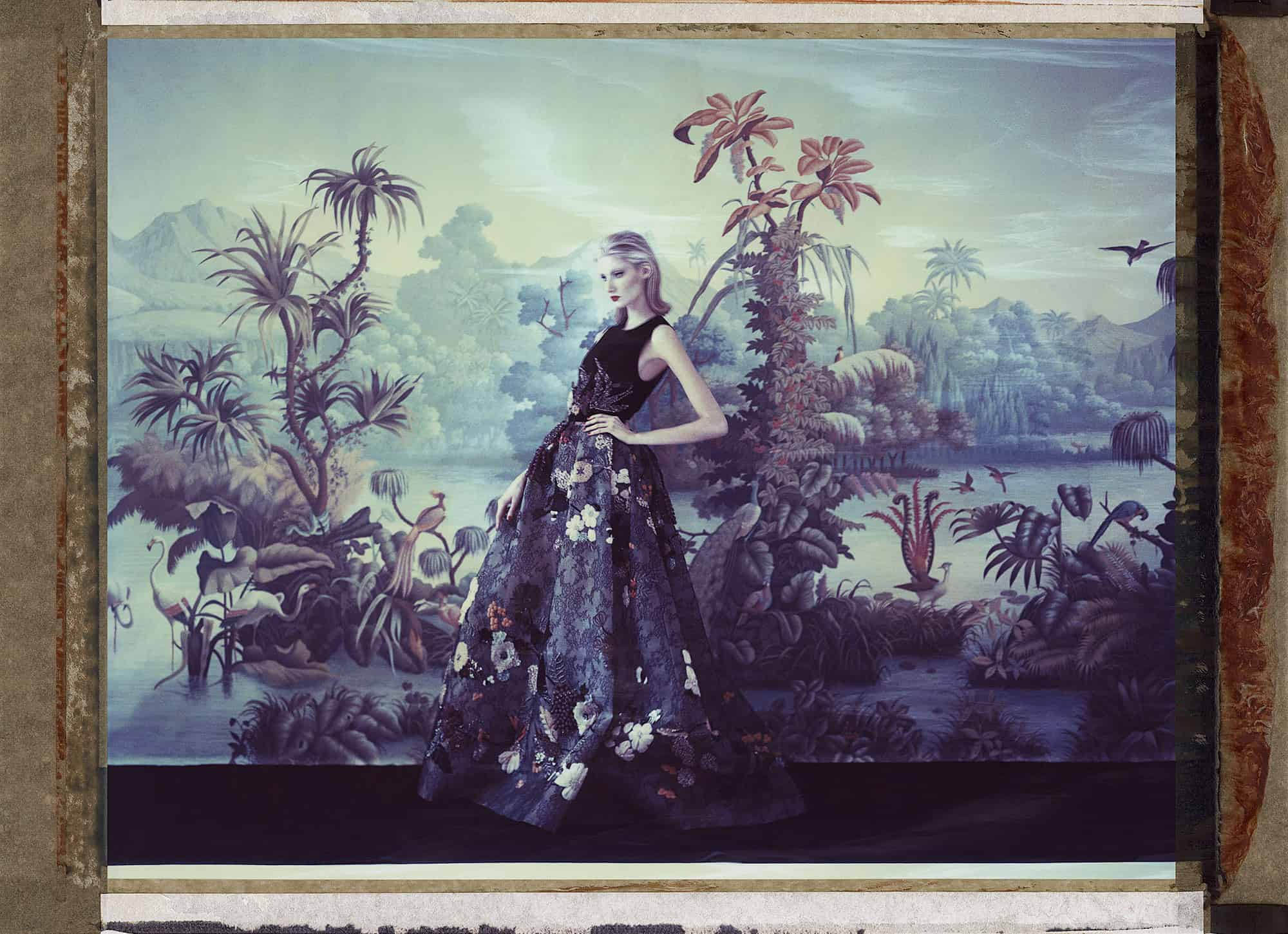 Fine art color photography of fashion model wearing haute couture by Elie Saab in front of a painted wallpaper depicting jungle in Brazil. Wallpaper by de Gournay.