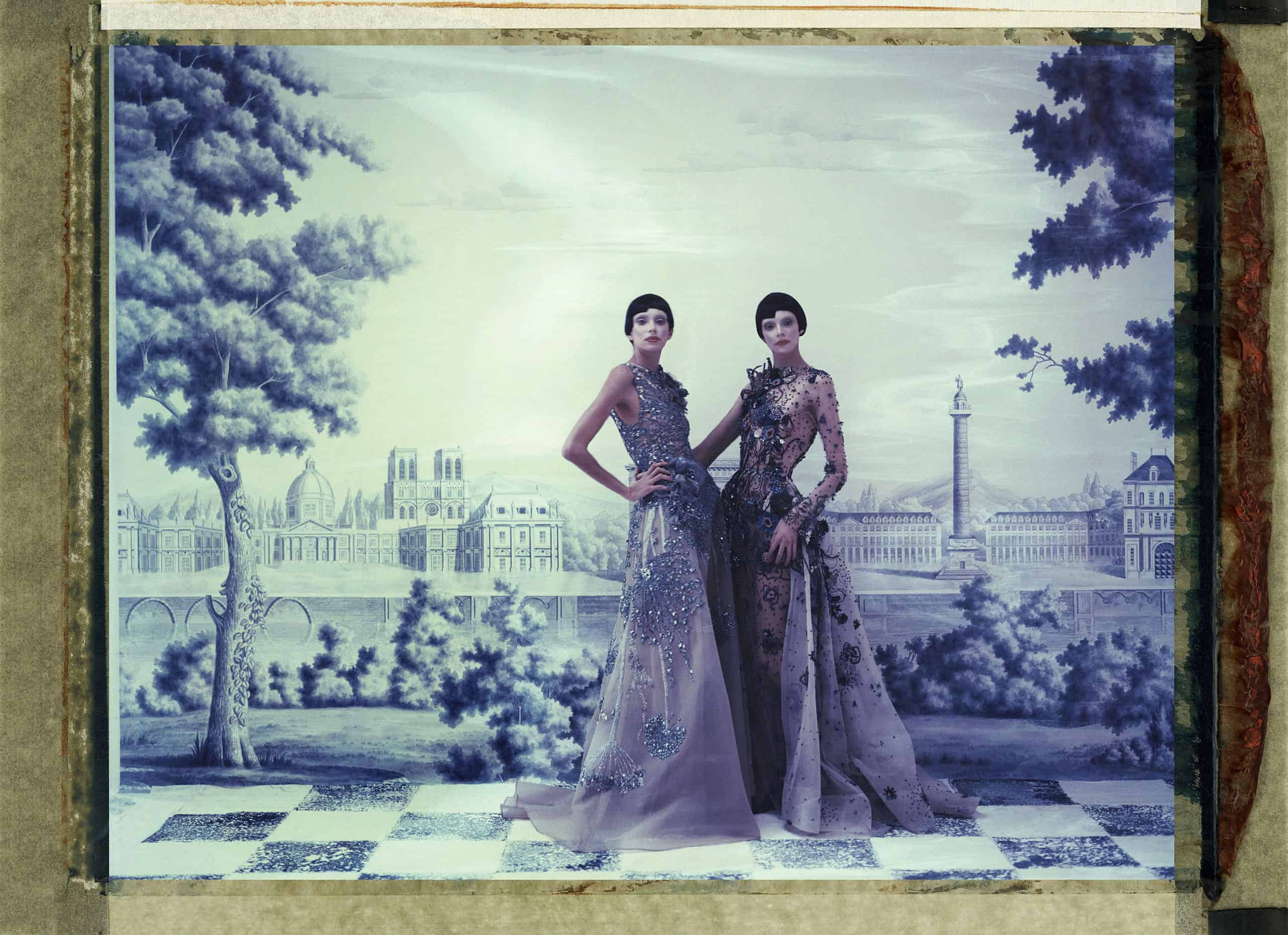 Fine art color photography of two twin fashion model wearing haute couture by Elie Saab, in front of a painted wallpaper depicting historic Paris. Wallpaper by de Gournay.