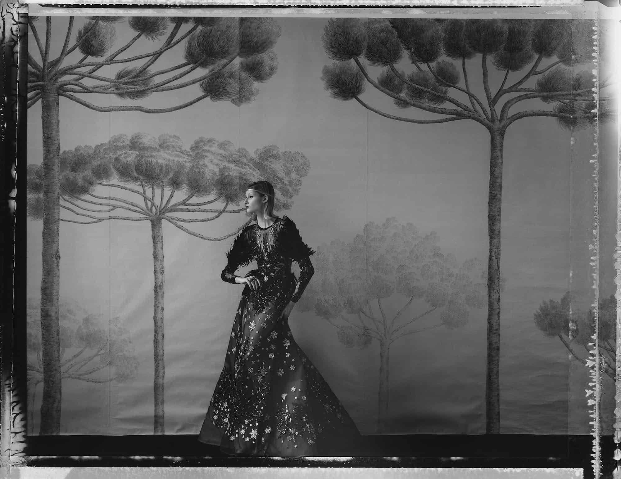 Fine art b/w photography of fashion model wearing haute couture by Elie Saab, in front of a painted Wallpaper depicting a forest. Wallpaper by de Gournay.