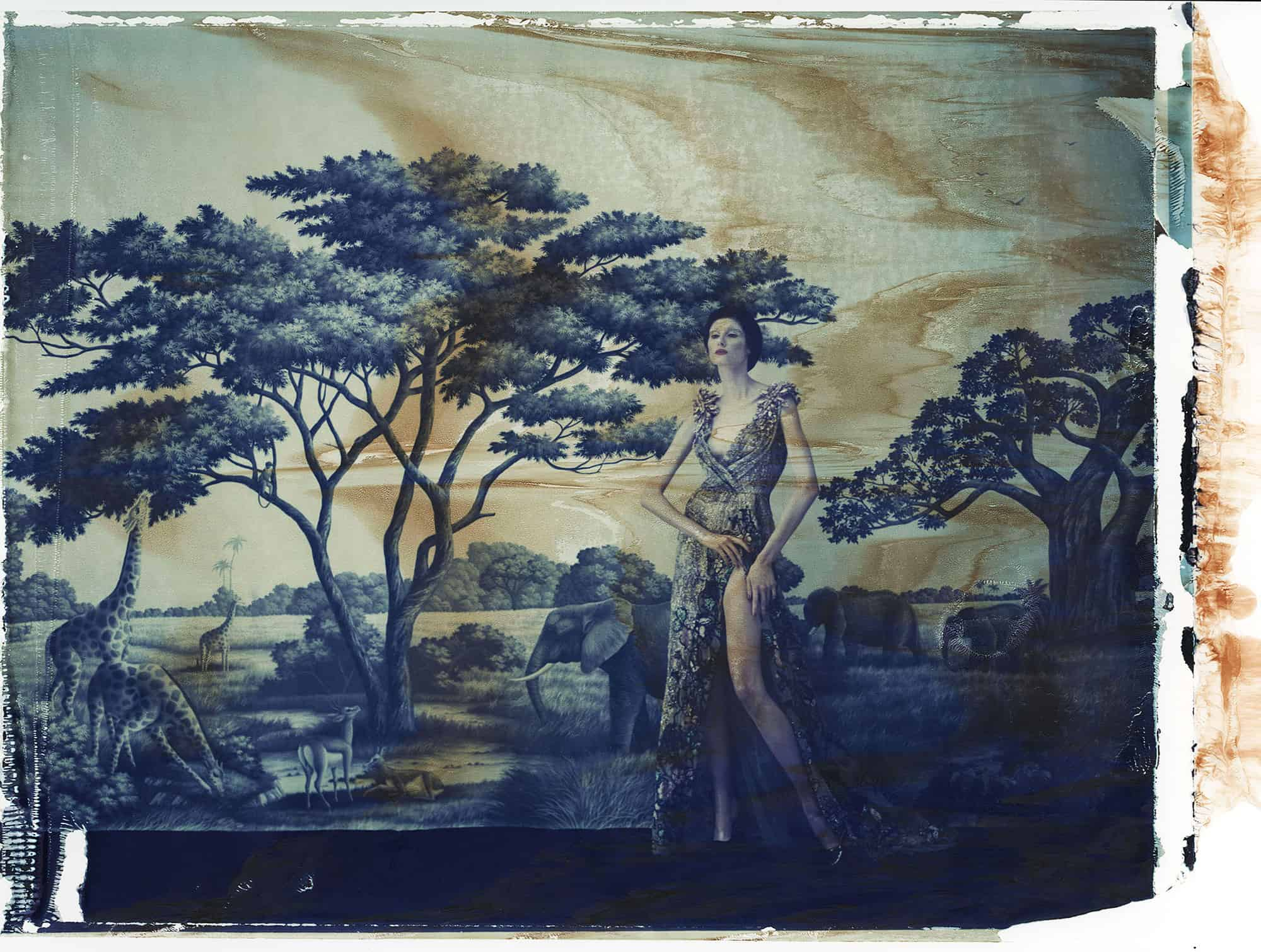 Fine art color photography of fashion model wearing haute couture by Elie Saab in front of a painted wallpaper depicting the Serengti, Africa, with elephants, giraffes and antelopes. Wallpaper by de Gournay.