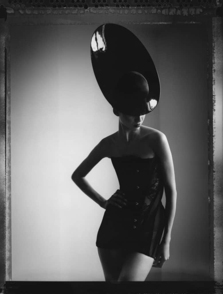 Fine art b/w photography of a fashion model wearing haute couture hat by Philip Treacy.
