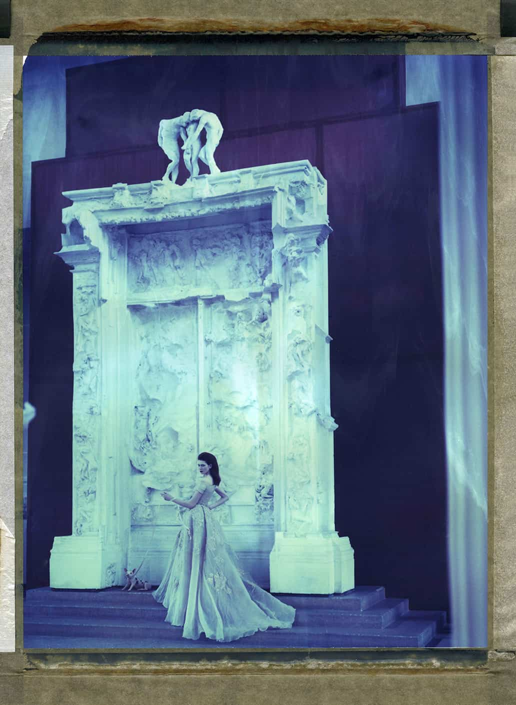 "Fine Art color photography with fashion model wearing Haute Couture by Elie Saab and holding a piglet at a leash. Photographed in front of August Rodin's plaster cast of ""The Gates of Hell"" at the Musée Rodin Meudon, France"