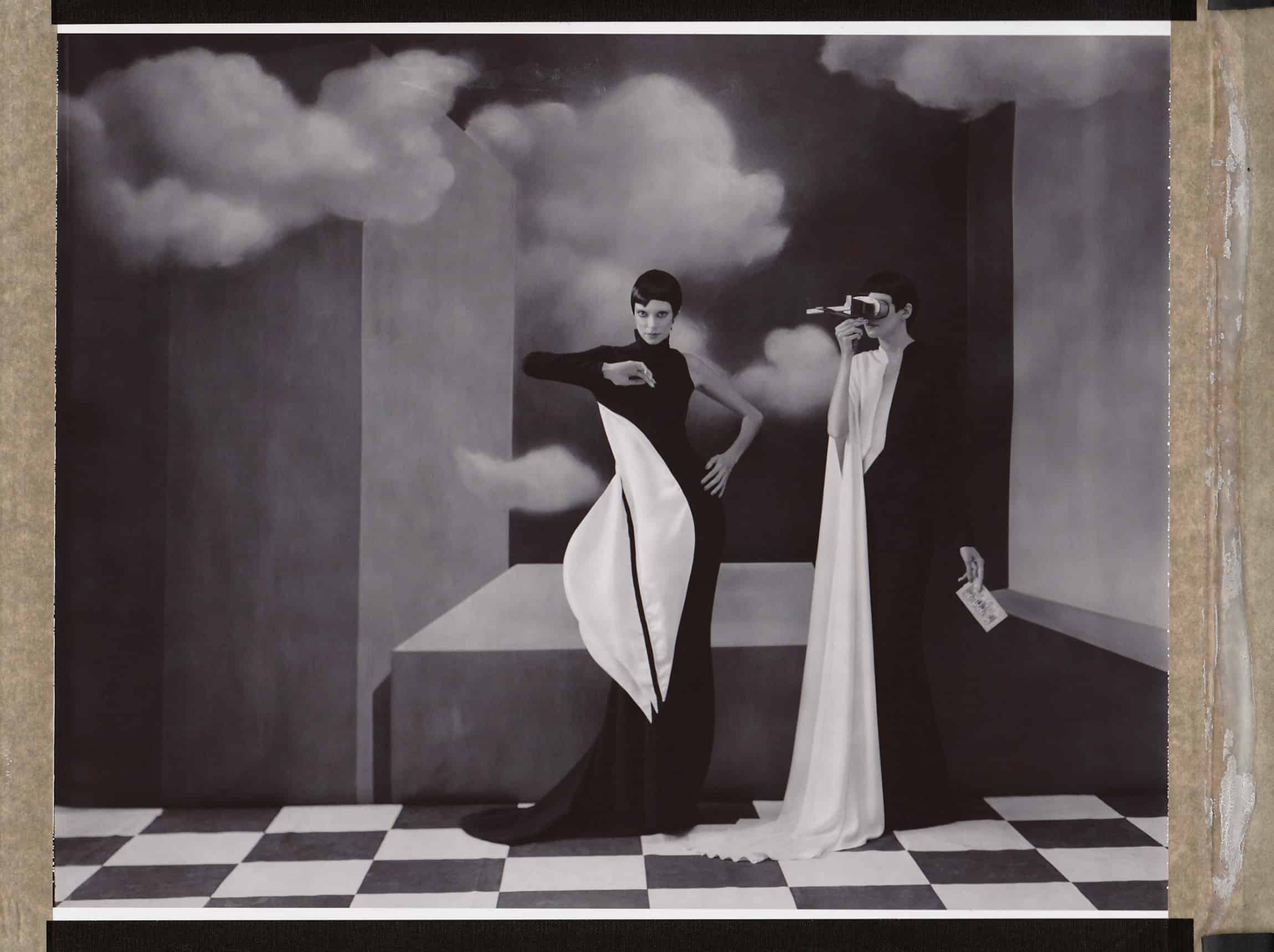 Fine Art b/w photography of twin fashion models wearing haute couture by Stephane Rolland. Handpainted backdrop inspired by René Magritte paintings