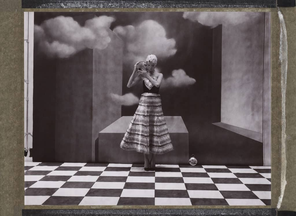 Fine Art b/w photography of fashion model wearing haute couture by Schiaparelli. Handpainted backdrop inspired by René Magritte paintings.