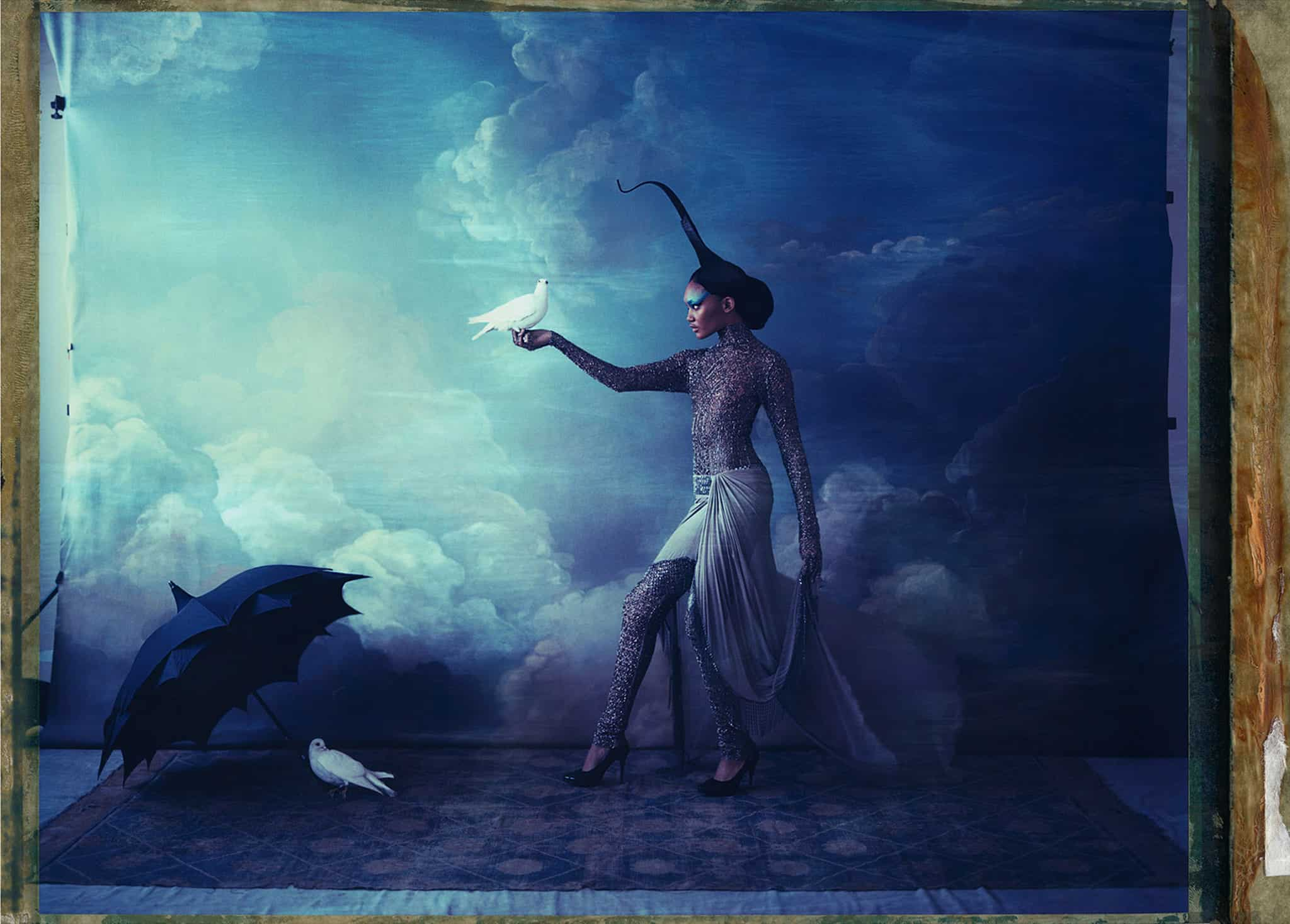 Fine art color photography of a fashion model wearing haute couture by Rami al Ali and hat by Philip Treacy, with two doves. Hand-painted backdrop of sky.