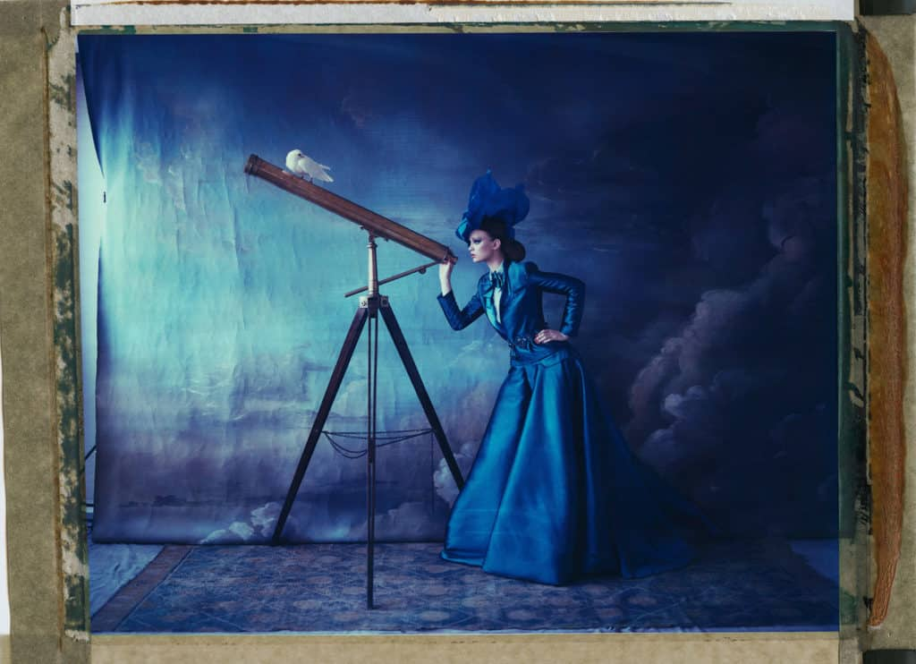 Fine art color photography of a fashion model wearing haute couture by Alexis Mabille, with telescope. Hand-painted backdrop with sky.