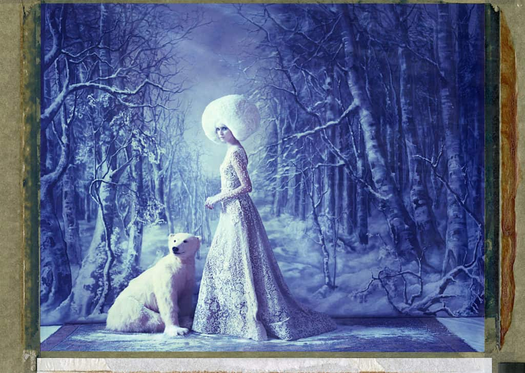 Fine art color photography of a fashion model wearing haute couture by Elie Saab and stuffed ice bear, with hand-painted Taiga forest backdrop.
