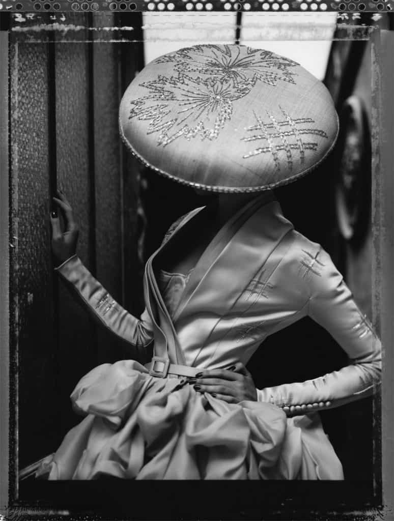 Fine art b/w photography of a fashion model wearing haute couture DIOR by John Galliano, hat by Steven Stones.