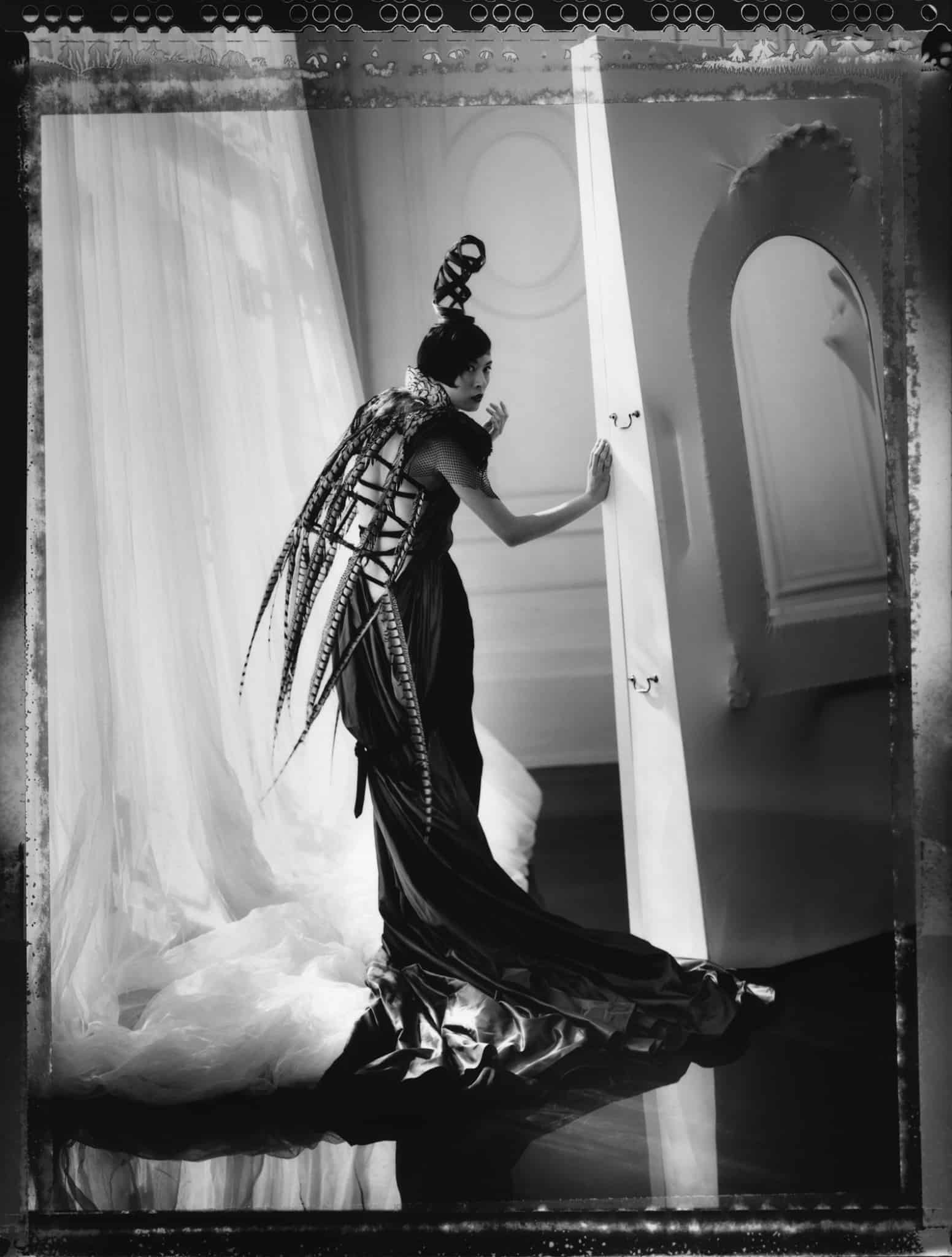 Fine art b/w photography of a fashion model wearing haute couture by John Paul Gaultier, hair by Odile Gilbert, photographed at Gaultier haute coutre show room, Paris.