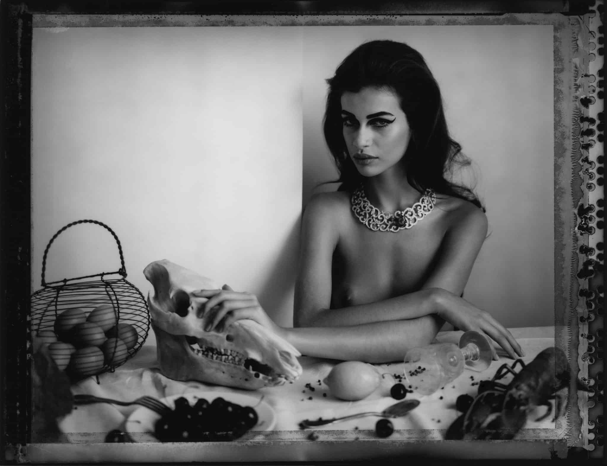 Fine art b/w photography of semi-nude fashion model wearing jewellery necklace and ring by Boucheron, sitting on a table with a horse skull, lobster, e.g., influenced by flemish still life paintings.