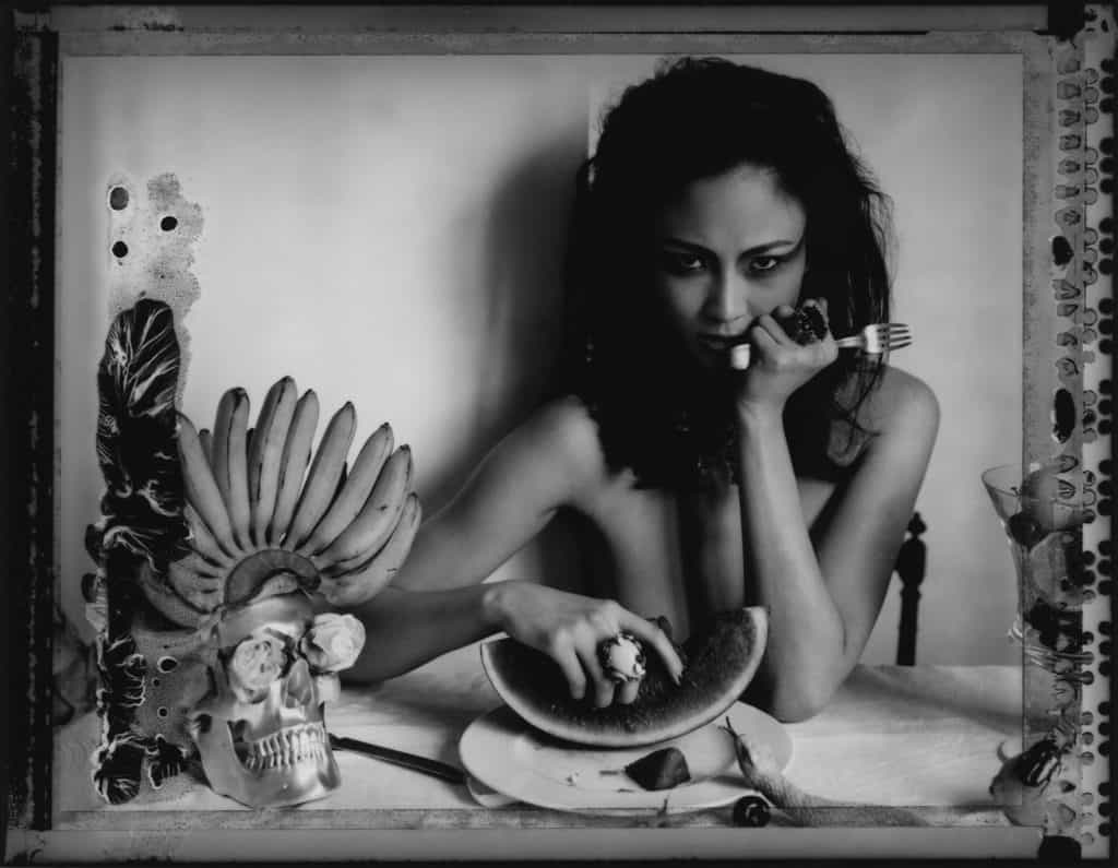 Fine art b/w photography of semi-nude fashion model wearing jewellery necklace and rings by DIOR, sitting on a table with a skull, bananas, e.g., influenced by Frida Kahlo paintings.