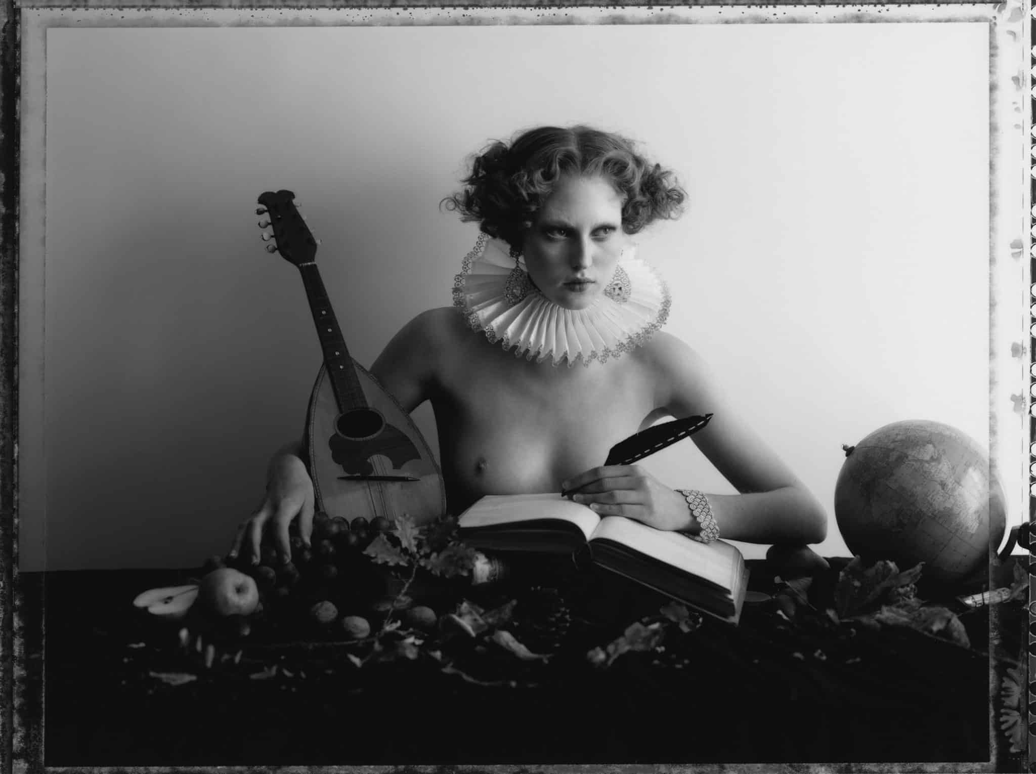 Fine art b/w photography of semi-nude fashion model wearing Buccellati jewellery, ear rings and bracelet, sitting on a table with various object like a mandoline, a globe and fruits. Influenced by english still life paintings.