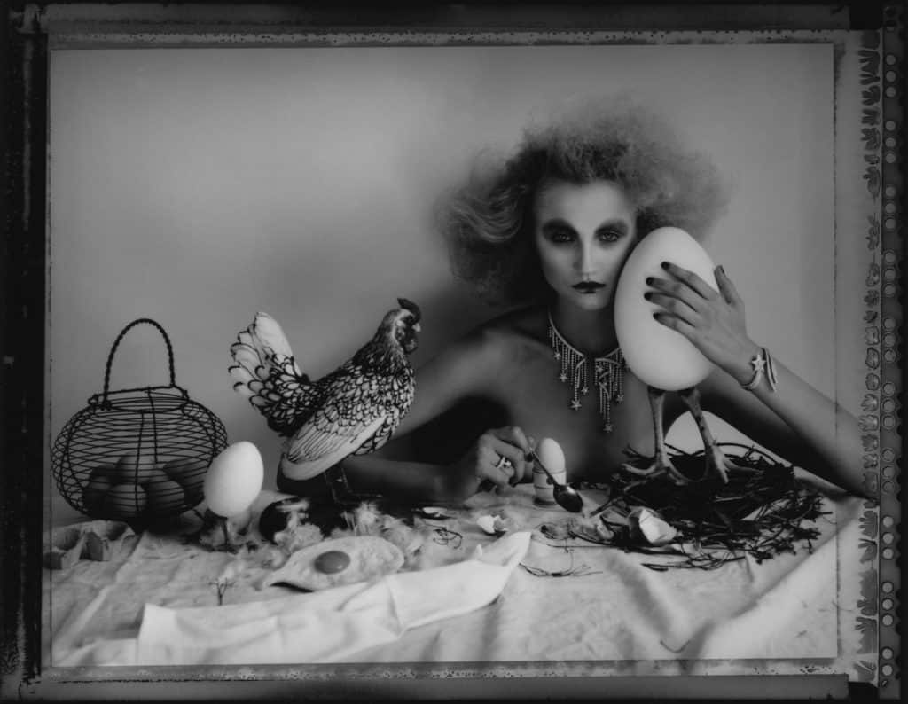 Fine art b/w photography of semi-nude fashion model wearing Chanel jewellery, necklace, bracelet, ring,, sitting on a table with a stuffed chicken and eggs.