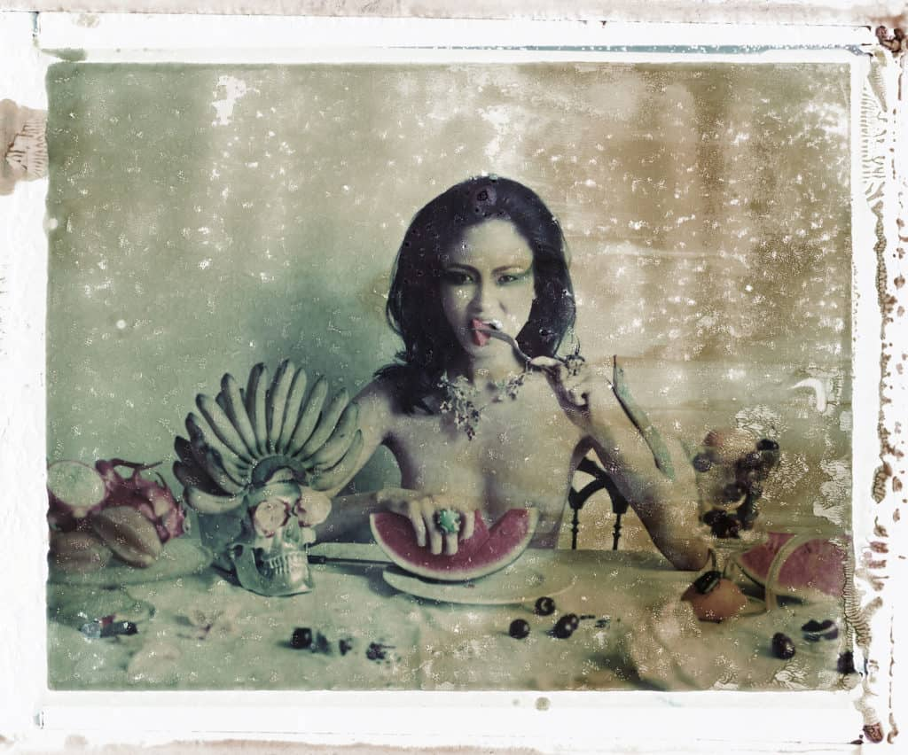 Fine art color photography of semi-nude fashion model wearing DIOR jewellery, necklace and rings, on a table with various objects: skull, fruits and flowers. Inspired by Frida Kahlo paintings.