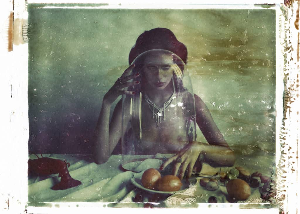 Fine art color photography of semi-nude fashion model wearing Boucheron jewellery, necklace and ring, sitting on a table with fruits, lobster, e.g. Influenced by flemish still life paintings.