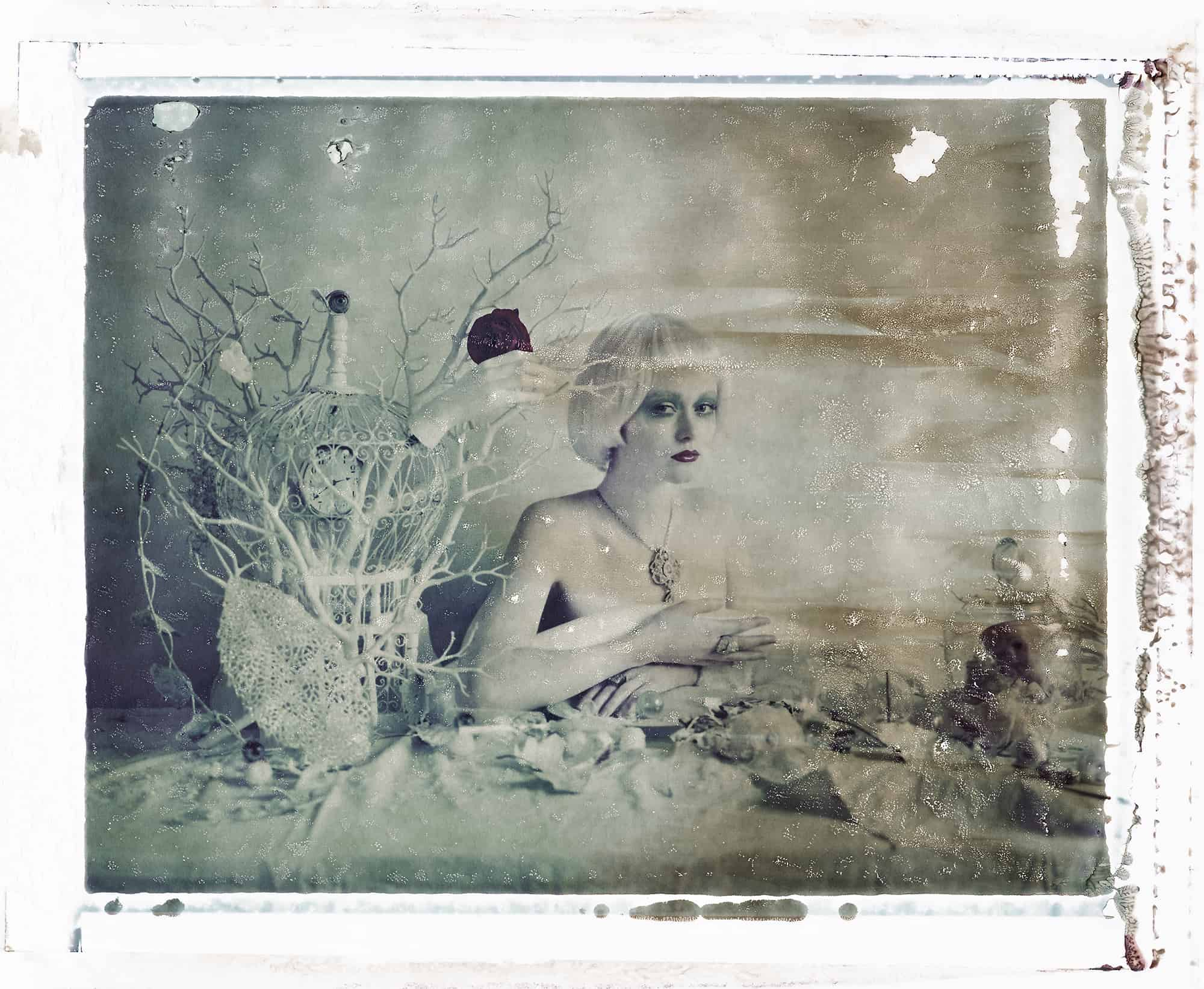 Fine art b/w photography of semi-nude fashion model wearing Reposi jewellery, necklace, rings, sitting on a table with bird cage, snow balls, glass eyes e.g.,. Inspired by Surrealist paintings.